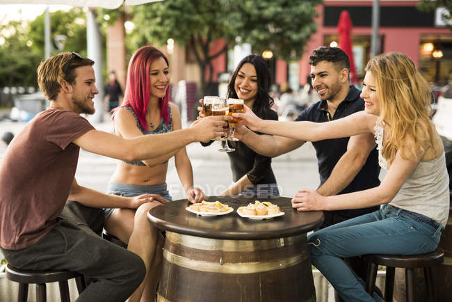 Friends toasting with beer glasses in outdoor bar — Stock Photo