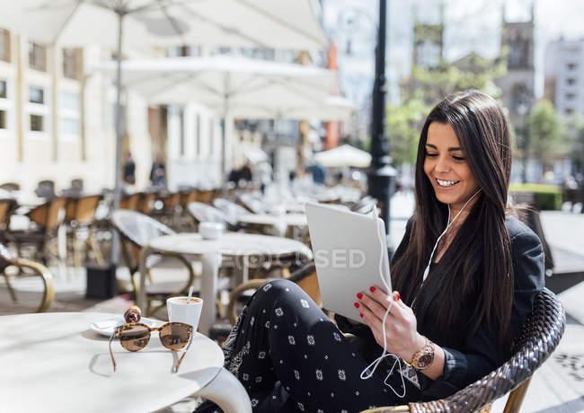 Красивая молодая женщина пьет кофе с помощью цифрового планшета, слушает музыку в кафе на тротуаре — стоковое фото