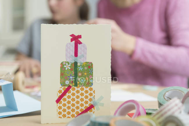 Closeup of birthday card with people in background — Stock Photo