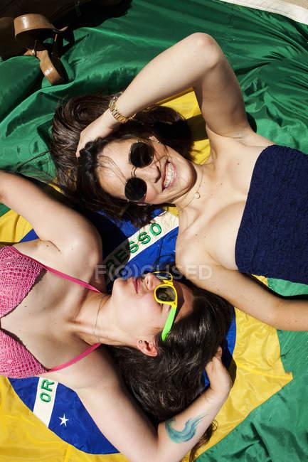 Two friends wearing beachwear, lying on Brazilian flag — Stock Photo