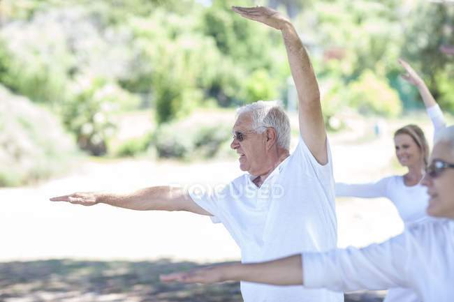 Старший мужчина растягивает руки во время занятий йогой — стоковое фото