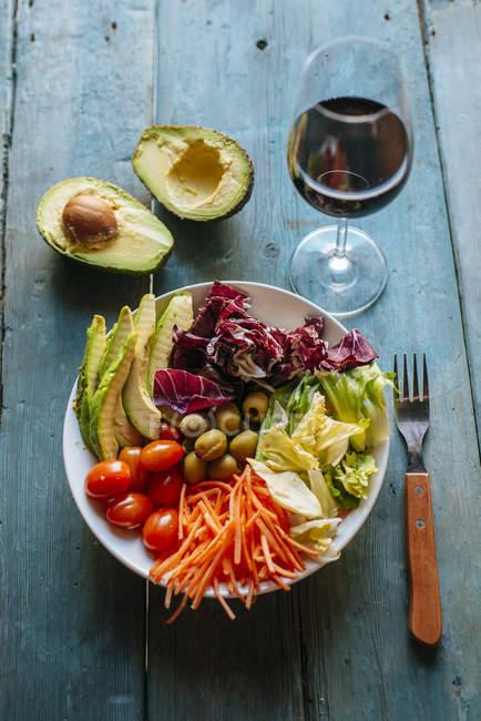 Салат с нарезанный авокадо и стакан красного вина — стоковое фото