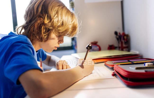 Портрет задумливою хлопчик робить домашнє завдання в домашніх умовах — стокове фото