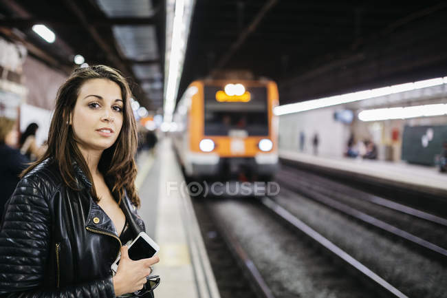 Young woman on train station awaiting train coming in — Stock Photo