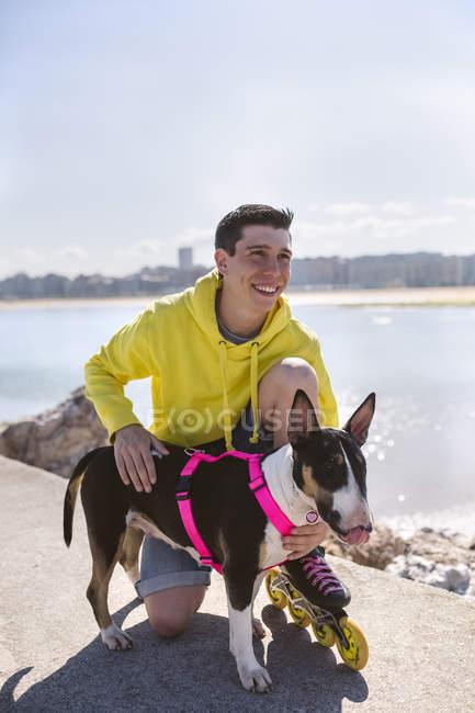 Porträt des Lächelns Inline-Skater mit seinen Bullterrier — Stockfoto