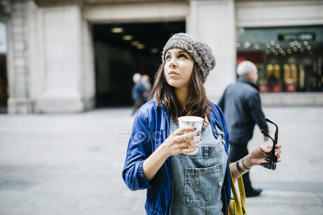 Spain, Barcelona, young woman with a coffee in the city — Stock Photo