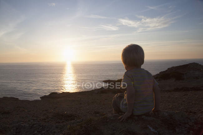 Back view of little boy watching sunset — Stock Photo