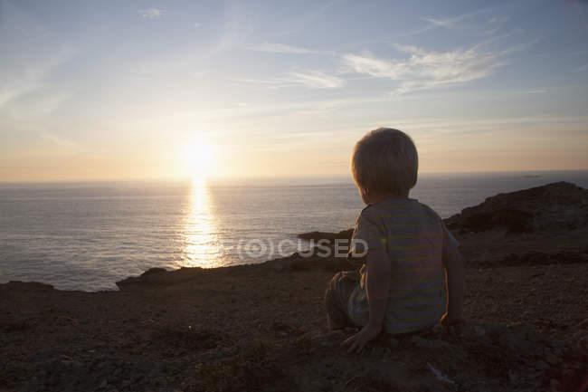 Visão traseira do menino assistindo pôr do sol — Fotografia de Stock
