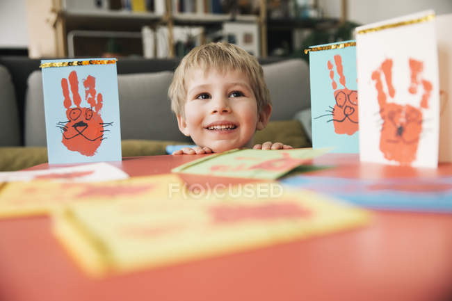 Little boy creating Easter cards with hand prints at home — Stock Photo