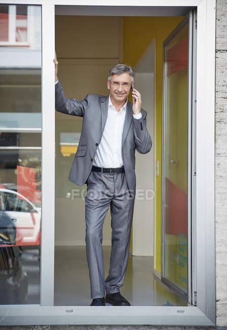 Homme d'affaires debout dans la porte de son bureau, tenant téléphone mobile — Photo de stock