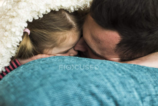 Father and daughter cuddling at home under blanket — Stock Photo