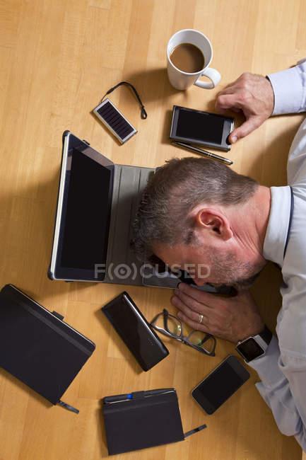 Businessman lying on laptop — Stock Photo
