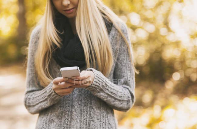 Adolescente sosteniendo teléfono celular en el bosque - foto de stock