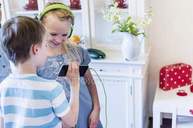 Crianças com telefone celular e fones de ouvido — Fotografia de Stock