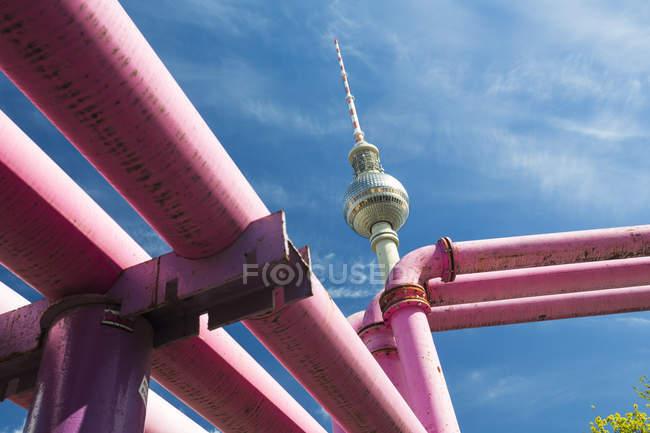 Alemania, Berlín, ve a la torre de la televisión con tubos de color de rosa en primer plano - foto de stock