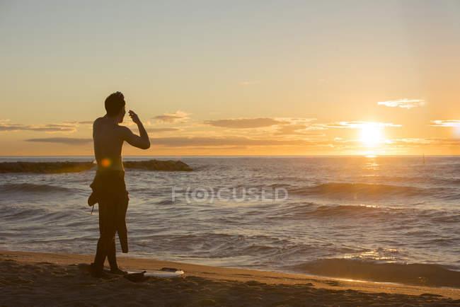 Visão traseira do surfista em pé na praia assistindo ao nascer do sol — Fotografia de Stock