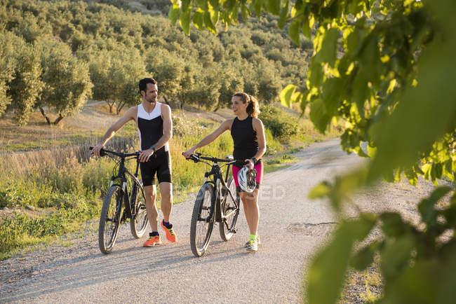 Deportiva hombre y mujer empujando bicicletas y hablando en paisaje rural - foto de stock