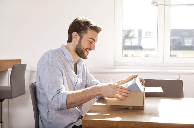 Young man sitting at a table unpacking cardboard box — Stock Photo