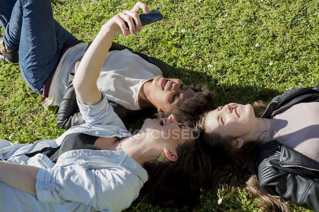 Tre amiche sdraiate sull'erba scattare selfie con smart phone, vista elevata — Foto stock