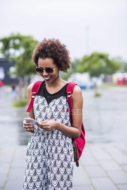 Porträt einer lächelnden jungen Frau, die auf ihr Smartphone blickt — Stockfoto