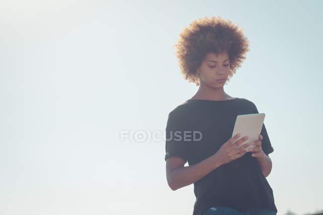 Donna alla retroilluminazione guardando tablet digitale — Foto stock
