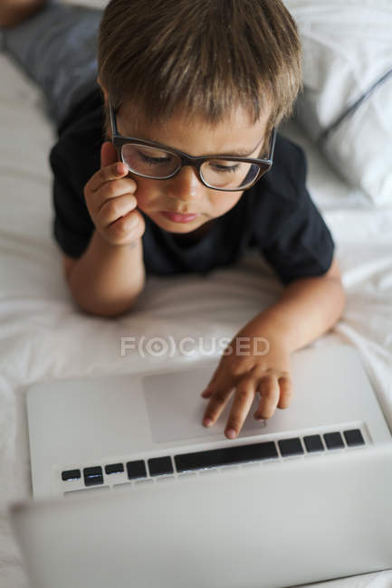 Маленький хлопчик в окулярах, лежачи на ліжку, використовуючи ноутбук — стокове фото