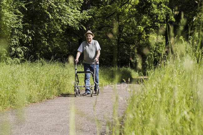 Senior man strolling with wheeled walker in nature — Stock Photo