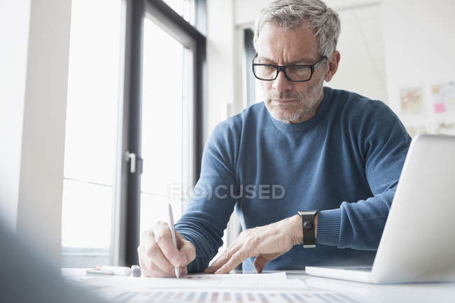 Mature man sitting in office working with laptop and smart watch — Stock Photo