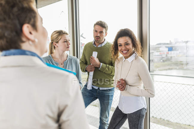 Three colleagues and mature woman in office — Stock Photo