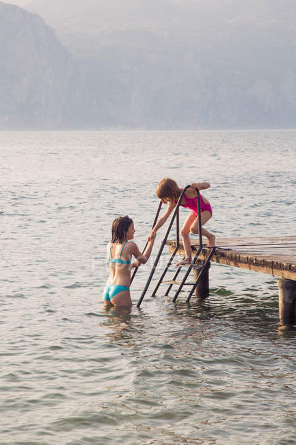 Italia, Brenzone, Chica ayudando a su hermana a venir de embarcadero a lago de agua - foto de stock