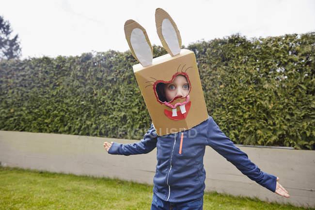 Garçon portant des commandes de masque de lapin dans le jardin — Photo de stock