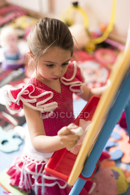 Little girl drawing on chalk board in children's room — Stock Photo
