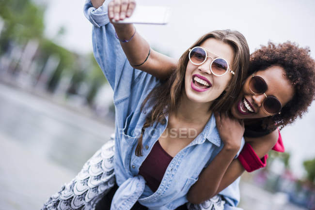 Portrait of two happy best friends taking selfie with smartphone — Stock Photo
