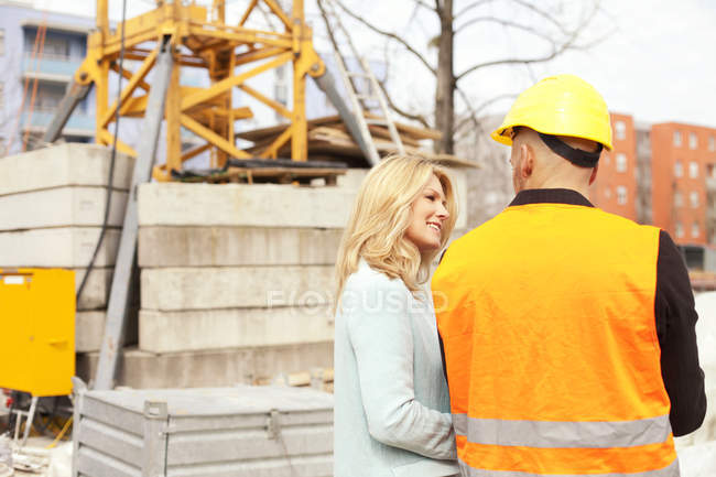 Woman looking at man with hard hat on construction site — Stock Photo