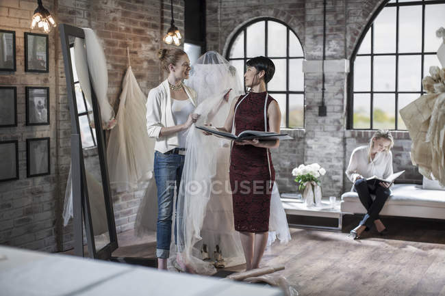 Wedding dress designer and bride to be talking in bridal store — Stock Photo