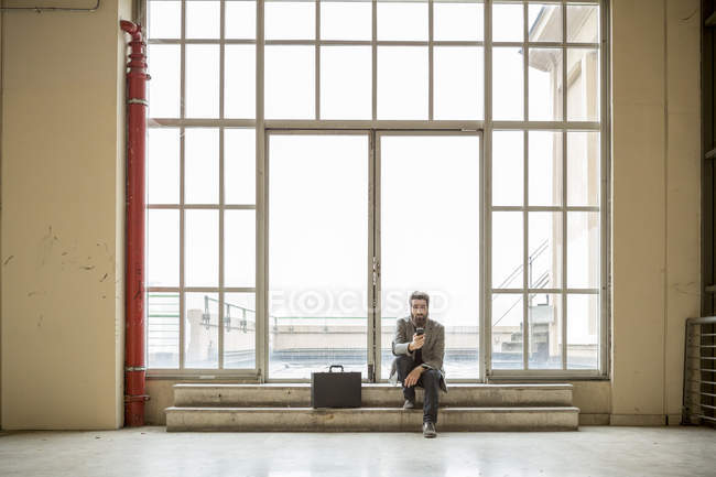 Hipster businessman with briefcase waiting in front of door in industrial building — Stock Photo