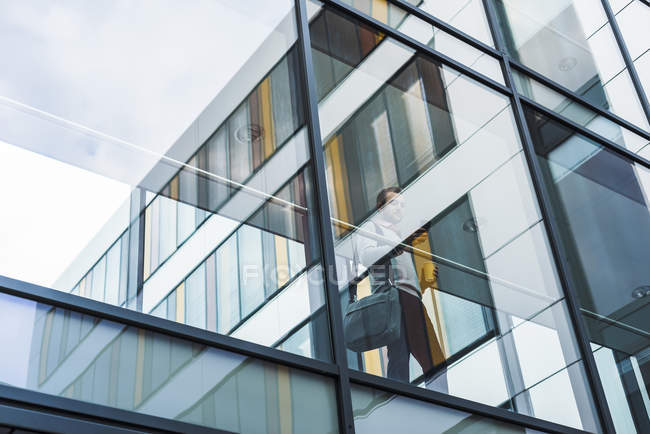 Uomo d'affari con cellulare, in piedi in passaggio — Foto stock
