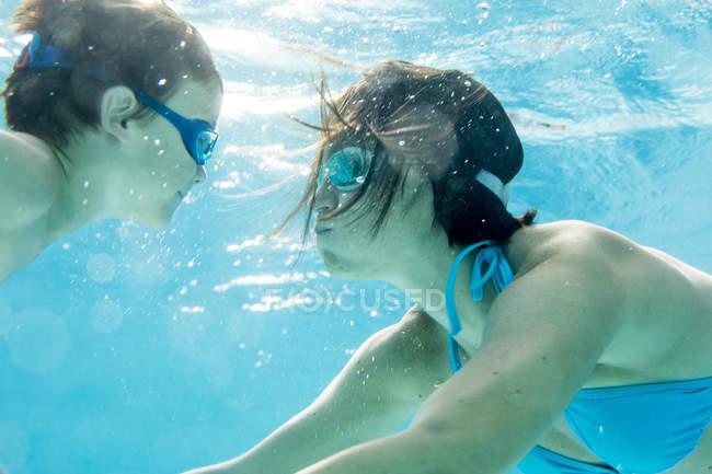 Мальчик в Подводный дайвинг с мамой в бассейне — стоковое фото