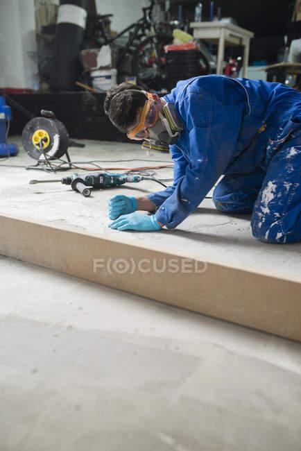 Проверка уровня бетонного пола работника — стоковое фото