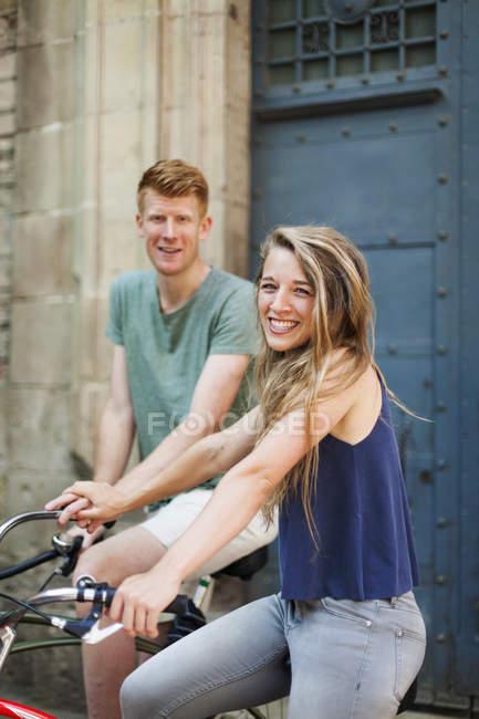 Porträt einer lachenden Frau mit Fahrrad an der Hand mit ihrem Freund im Hintergrund — Stockfoto