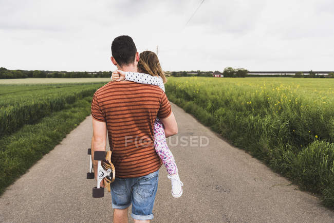 Padre con monopatín llevando a su hija en el carril del país - foto de stock