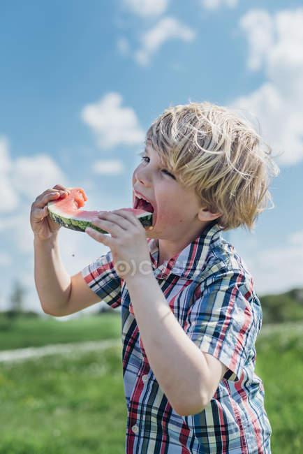 Ragazzo mangiare fetta di anguria — Foto stock