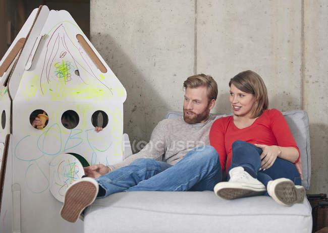 Pais olhando para a filha dentro do foguete de papelão — Fotografia de Stock
