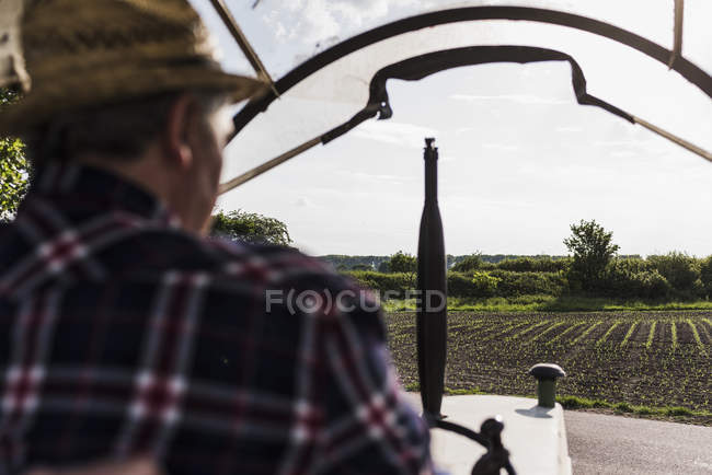Farmer on tractor next to field — Stock Photo