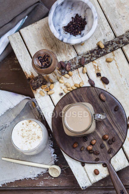 Top  view of three glasses of different smoothies with nuts and beans — Stock Photo