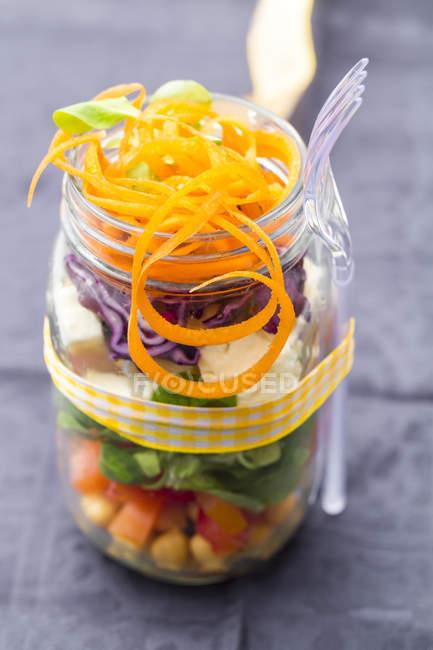 Радуга салат в стакан с нута, помидор, морковь, красная капуста, красный редис, салат и сыр фета сыр — стоковое фото