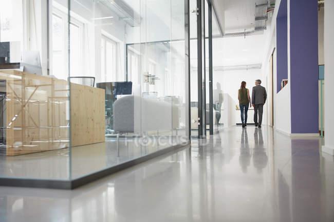 Uomo e donna d'affari camminano lungo il corridoio dell'ufficio — Foto stock