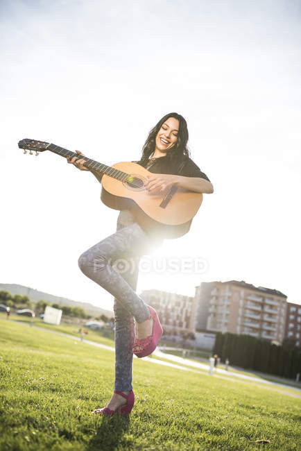 Happy young woman playing guitar — Stock Photo
