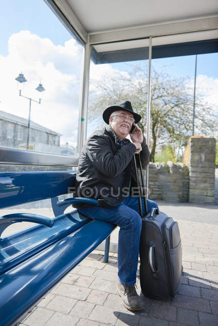 UK, Bristol, portrait of smiling senior man telephoning with smartphone while waiting at bus stop — Stock Photo