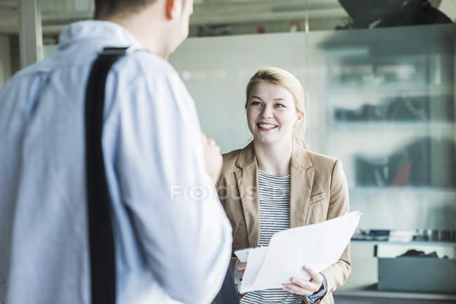 Двое его коллег в современном офисе говорить — стоковое фото